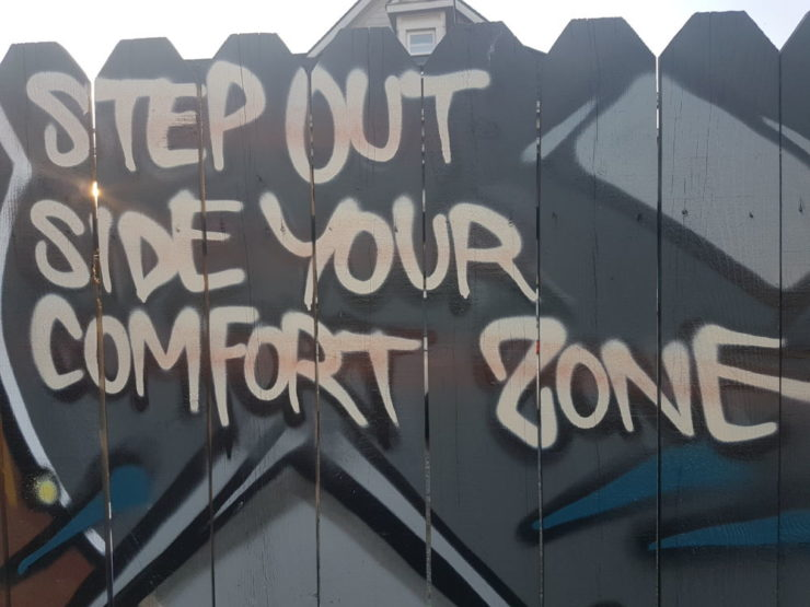 "Graffiti on a fence that reads ""Step out side your comfort zone."""