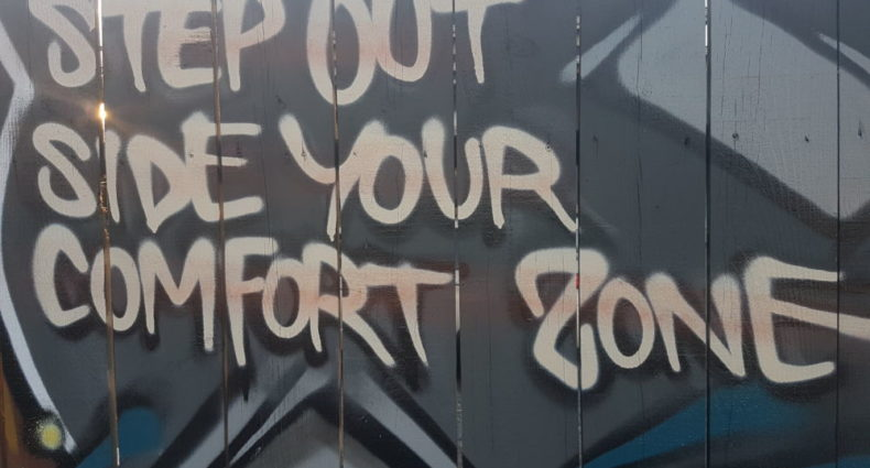 """Graffiti on a fence that reads """"Step out side your comfort zone."""""""