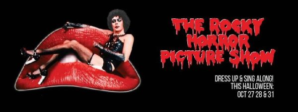 "Dr. Frank 'N Furter, a gender-ambiguous individual in black leather and garterbelts is stretched out across a pair of large red lips like they are a sofa. The background is entirely black with the text ""The Rocky Horror Picture Show"" typed out in spooky and bloody text. The dates for the Vic Theatre's showings are listed in white below - October 27, 28, and 31."
