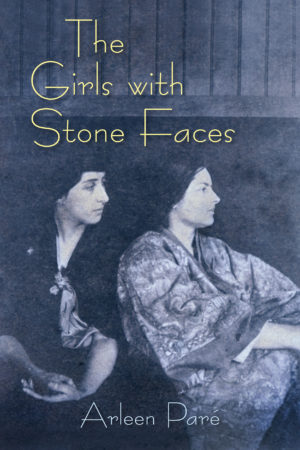 The book cover of The Girls with Stone Faces. Two women sit facing right on a blue-washed background. They are both wearing shawls around their shoulders and have their dark hair tied back from their faces.