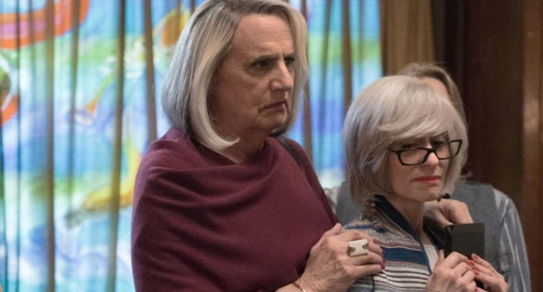 Jeffrey Tambor and Judith Light face right, looking worried or sad. Tambor plays a transgender woman with long greying hair and a red shawl, and Light plays a cisgender woman with short grey hair with bangs and a pair of dark glasses.