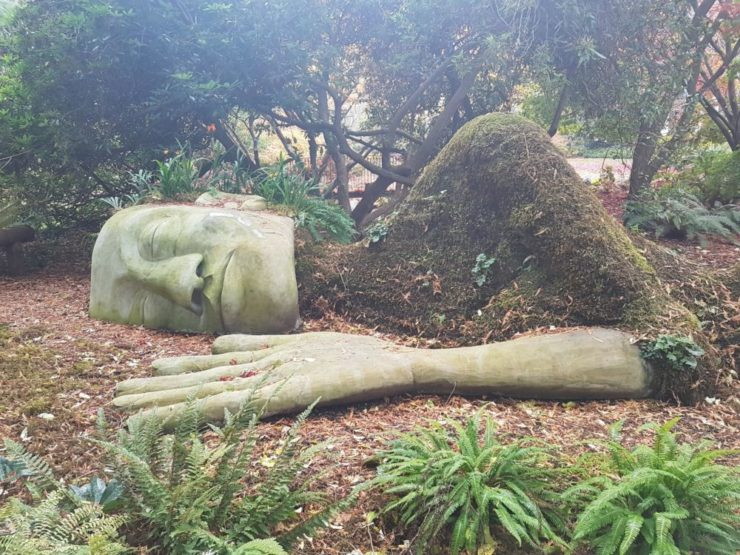 A statue of a large woman lying on her side, eyes closed. Her head and arm, which rests against the ground, are made of stone, while her body is a shaped mound of earth.