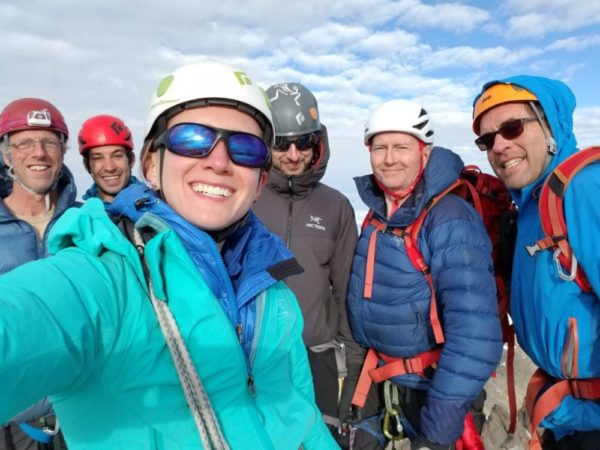 A woman dressed in bright blue mountaineering gear takes a selfie in front of five other climbers - all men - on top of a mountain.