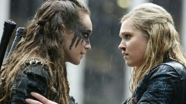 Alycia Debnam-Carey as Lexa, a woman with long brown hair and heavy black face paint, faces right as she looks at Eliza Taylor as Clarke Griffin, a blonde woman who has her hand resting on Lexa's upper arm.