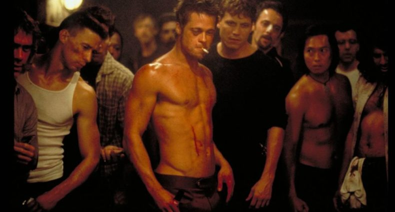 A group of sweaty, beaten men stand menacingly in a dark basement. Brad Pitt stands in the middle of the group, not wearing a shirt, his abdominal muscles flexed, a cigarette in his mouth, and a trail of blood down his stomach as he looks down at the floor towards an unseen person.