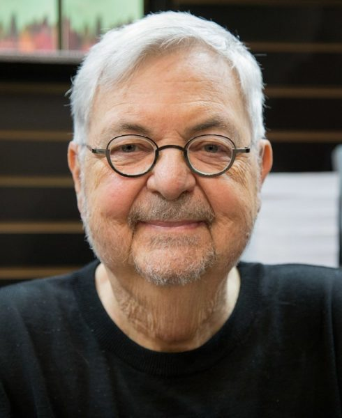 An older white man with short cropped grey hair and round glasses.