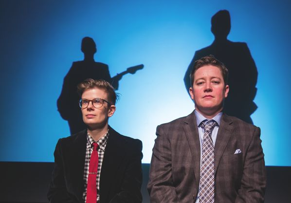 Rae Spoon and Ivan E Coyote, two nonbinary individuals in suits in front of a blue background with shadows.