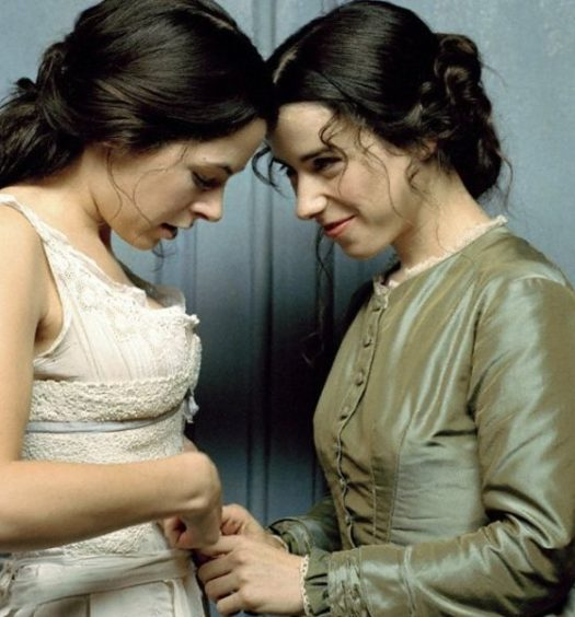 Two white women face each other - the one on the left looks down at her white Victorian undergarments while the one on the right, who is fully clothed, helps her undress while smiling secretively.