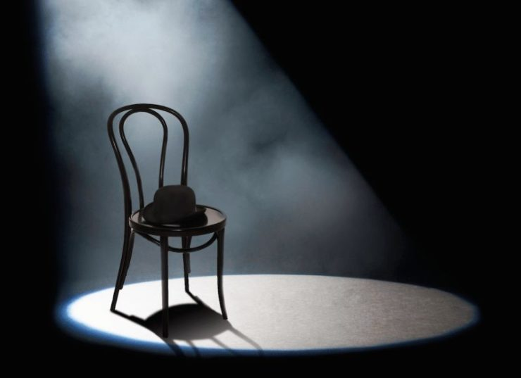 A metal-framed chair sitting in a spotlight.