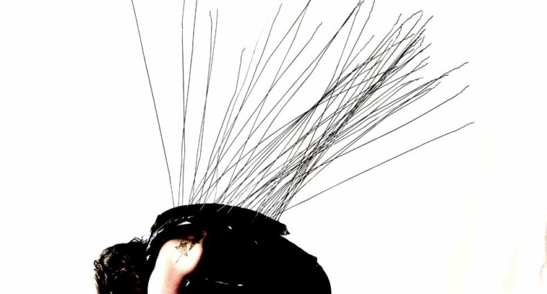 Crouched in front of a white background, a dancer in black leans over their legs, head bowed. Long black wires sprout from their back,, reaching upwards.