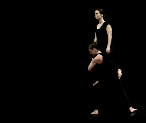In front of a black background, standing on a black floor, there are two female dressed in black athletic clothing. One is partially crouched, with her arms wrapped around the legs of the second dancer, who is being lifted into the air.