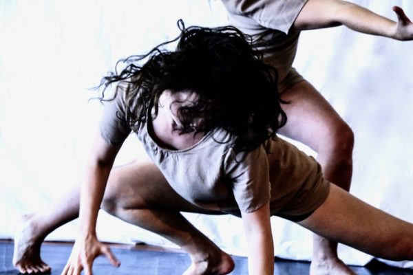 On a blue mat in front of a white wall, two dancers are photographed crouched while rotating their heads and bodies. In the foreground, one dancer has their long hair splaying wildly about while the background dancer spreads their arms wide.