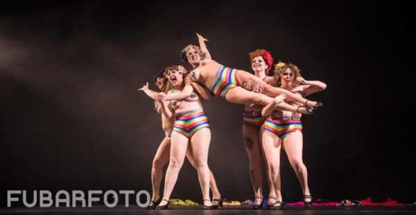 A group of fem burlesque dancers with striped rainbow underwear and nipple tassels hold up another woman who lies across her group members.
