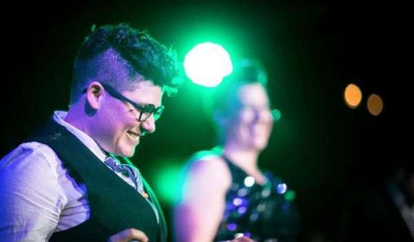A masculine individual with an undercut and glasses grins as they perform on stage. Behind them and out of focus is a feminine individual in a glittery outfit,