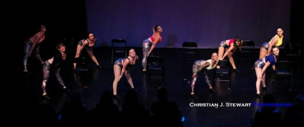 A group of femme dancers partially bent over chairs.