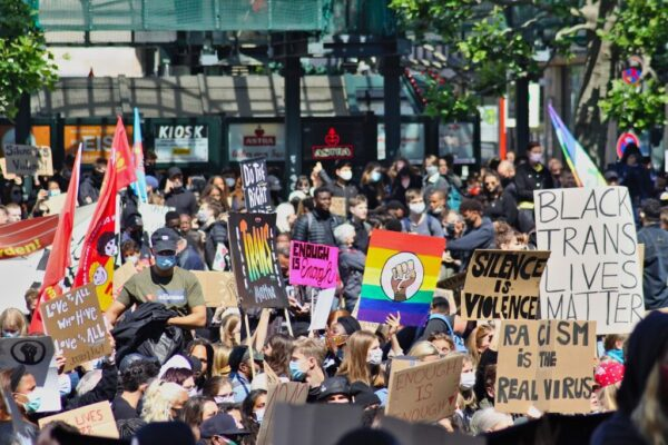 A crowd of people holding up Black Lives Matter signs, as well as signs with pride flags with an icon of a brown or black upheld fist in the centre.